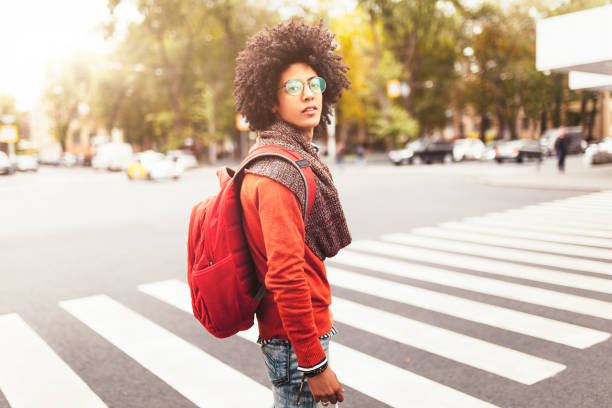 a young african american man with a red backpack crosses a crosswalk in a city - pedone ruolo dell'uomo foto e immagini stock