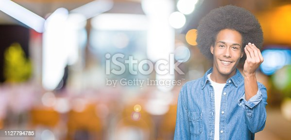 istock Young african american man with afro hair Doing Italian gesture with hand and fingers confident expression 1127794785