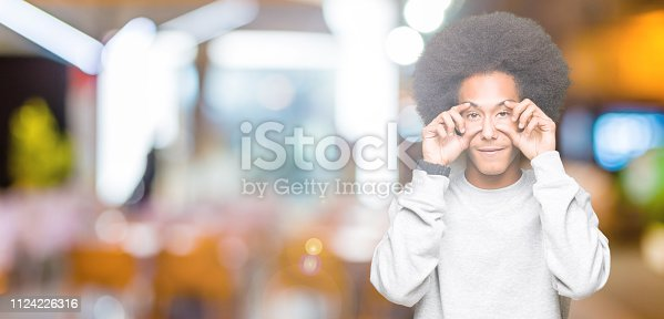 istock Young african american man with afro hair wearing sporty sweatshirt Trying to open eyes with fingers, sleepy and tired for morning fatigue 1124226316