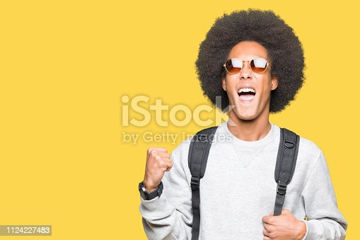 istock Young african american man with afro hair wearing sunglasses and backpack screaming proud and celebrating victory and success very excited, cheering emotion 1124227483