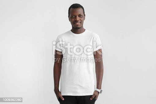 1018069806 istock photo Young african american man with dark skin standing with hands in pockets, wearing blank white t shirt with copy space for your logo or text, isolated on grey background 1009362260
