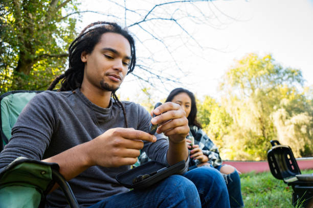 Young African American man with diabetes checking his blood sugar at a campsite in the woods stock photo