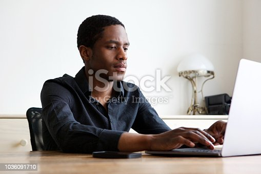 istock young african american man working on laptop at home 1036091710