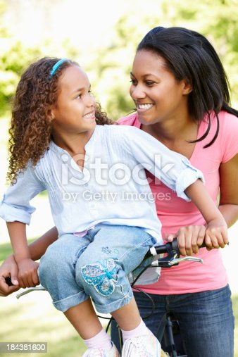 istock Young African American Mother And Daughter Cycling In Park 184381600