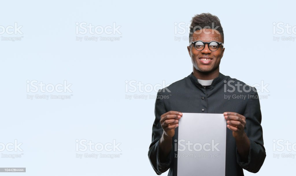 Young african american priest man over isolated background holding blank paper with a happy face standing and smiling with a confident smile showing teeth stock photo