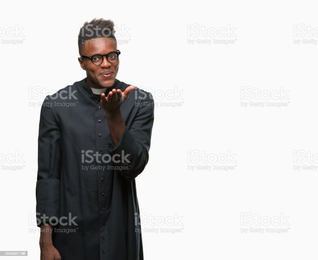 Young african american priest man over isolated background looking at the camera blowing a kiss with hand on air being lovely and sexy. Love expression. stock photo