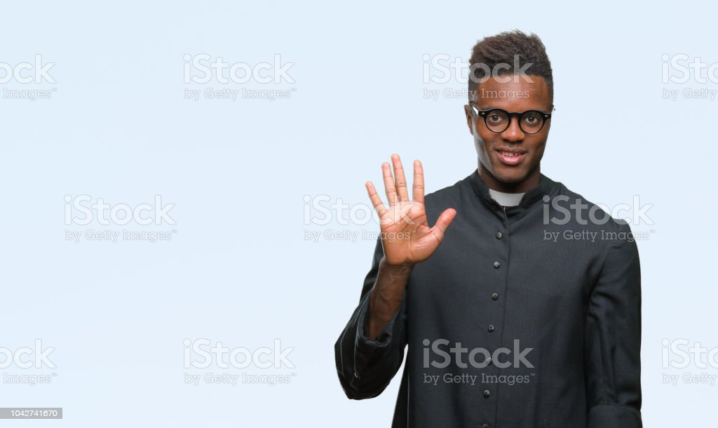 Young african american priest man over isolated background showing and pointing up with fingers number five while smiling confident and happy. stock photo