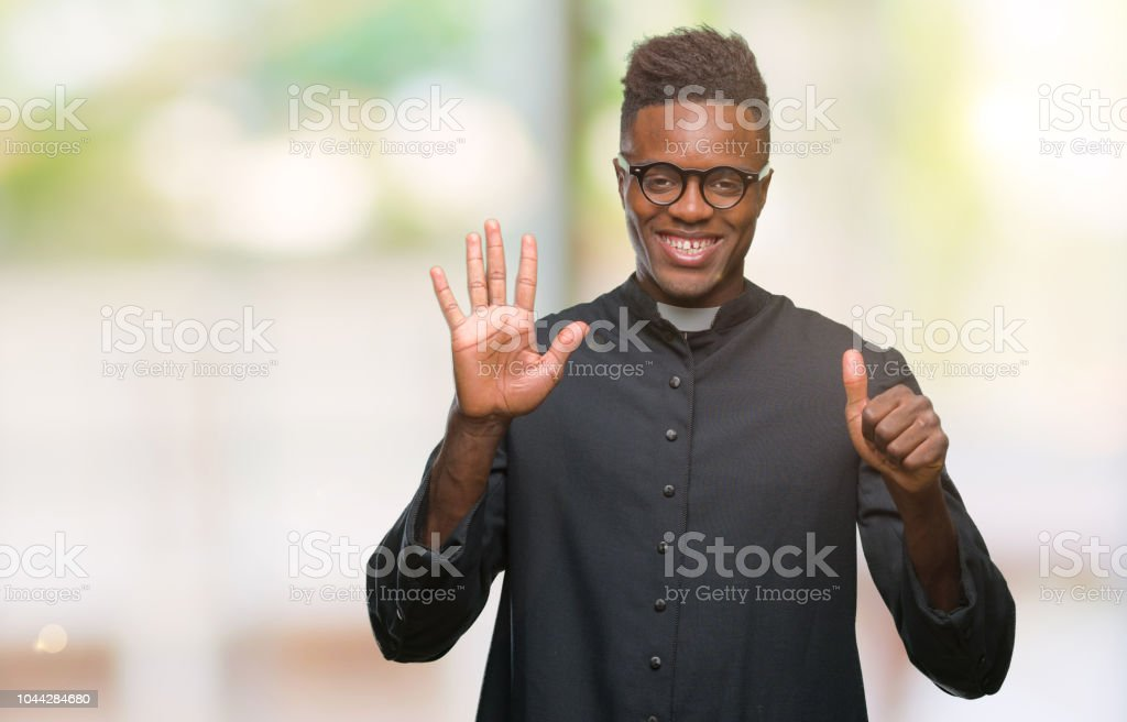 Young african american priest man over isolated background showing and pointing up with fingers number six while smiling confident and happy. stock photo