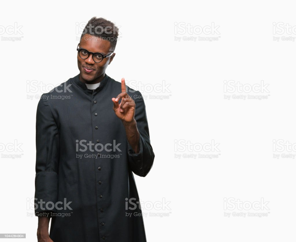 Young african american priest man over isolated background showing and pointing up with finger number one while smiling confident and happy. stock photo