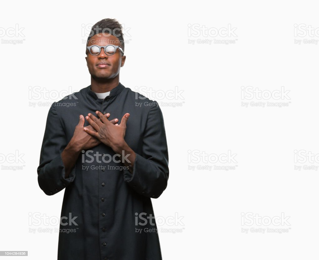 Young african american priest man over isolated background smiling with hands on chest with closed eyes and grateful gesture on face. Health concept. stock photo