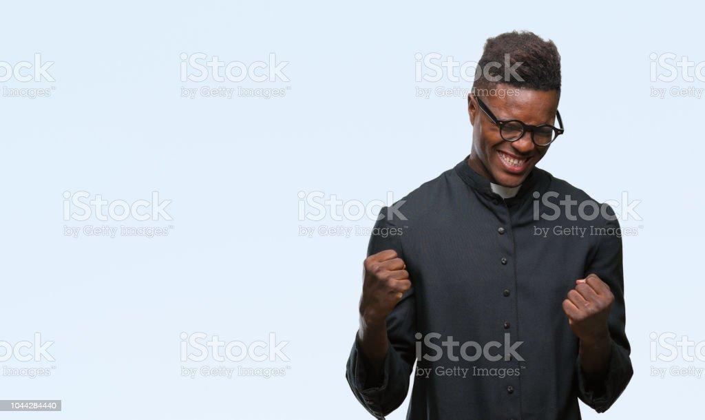 Young african american priest man over isolated background very happy and excited doing winner gesture with arms raised, smiling and screaming for success. Celebration concept. stock photo