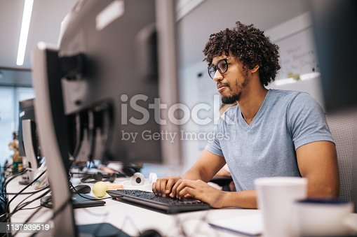 Young black computer programmer coding software while working on PC in the office.