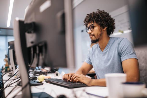joven programador afroamericano trabajando en pc de sobremesa en la oficina. - ingeniero fotografías e imágenes de stock
