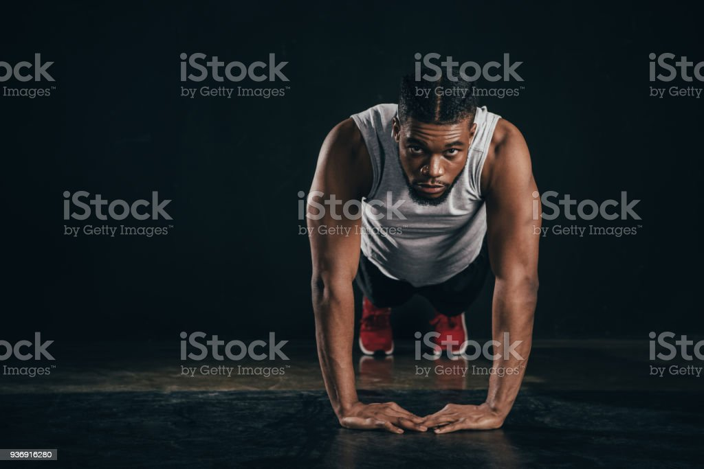 young african american sportsman doing plank position and looking at camera on black stock photo