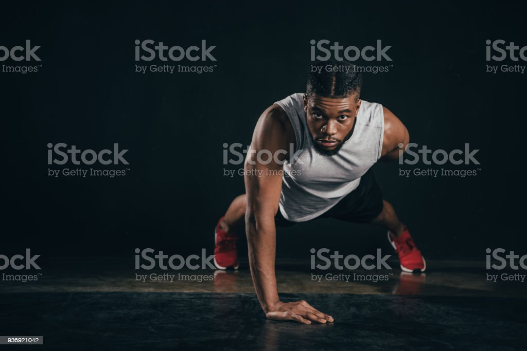 young african american sportsman doing push-ups and looking at camera on black stock photo