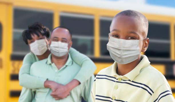 Young African American Student and Parents Near School Bus Wearing Medical Face Masks During Coronavirus Pandemic stock photo