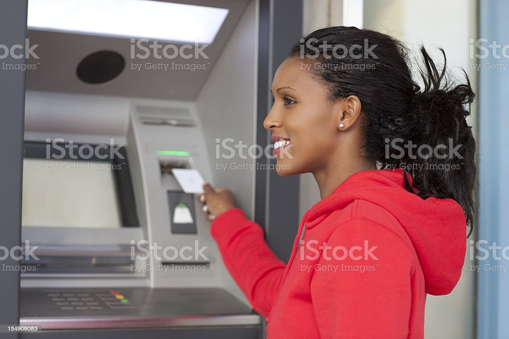 Young African American woman at an ATM wearing a red hoodie stock photo