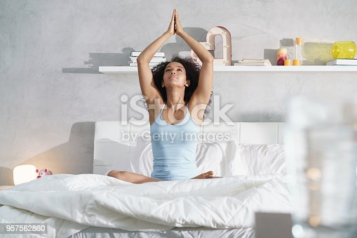 istock Young African American Woman Doing Yoga In Bed After Sleep 957562860