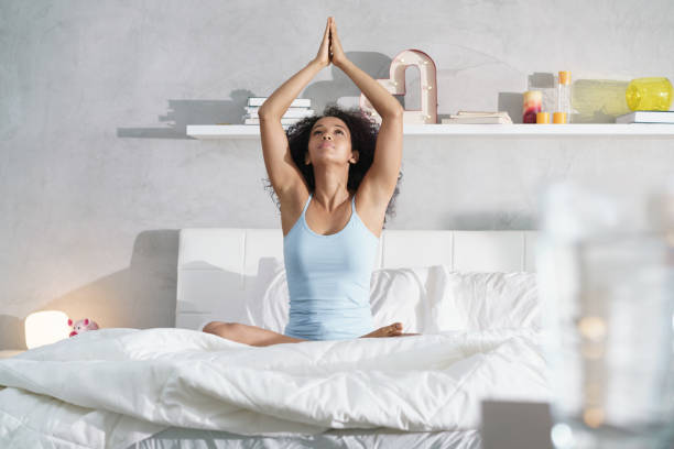 Young African American Woman Doing Yoga In Bed After Sleep stock photo