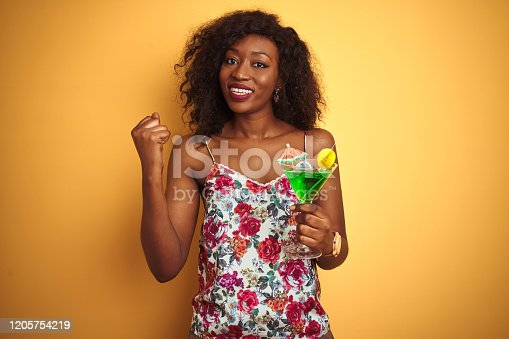 Young african american woman drinking cocktail standing over isolated yellow background screaming proud and celebrating victory and success very excited, cheering emotion