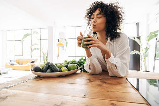 Young african american woman drinking green juice with reusable bamboo straw in loft apartment. Home concept. Healthy lifestyle concept. Copy space