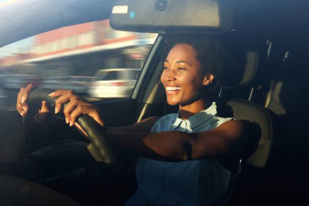 joven afroamericana conduciendo un coche - conducir fotografías e imágenes de stock