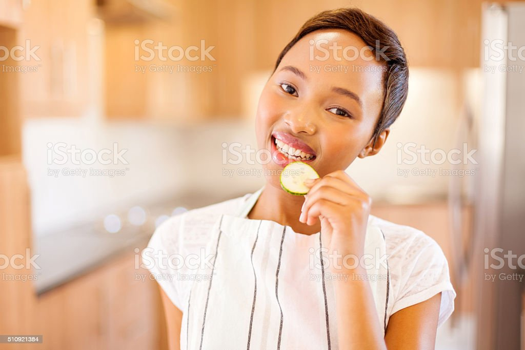 young african american woman eating a slice of cucumber stock photo