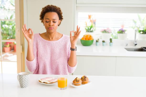 a mulher nova do americano africano que come breaksfast na manhã em casa relaxa e que sorri com os olhos fechados que fazem o gesto da meditação com dedos. conceito da ioga. - consciencia negra - fotografias e filmes do acervo