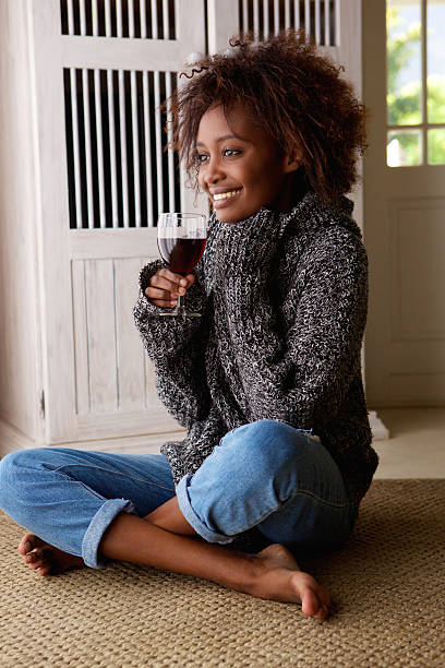 Young african american woman enjoying a glass of wine stock photo