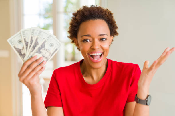 young african american woman holding bank notes of twenty dollars very happy and excited, winner expression celebrating victory screaming with big smile and raised hands - dollar bill стоковые фото и изображения