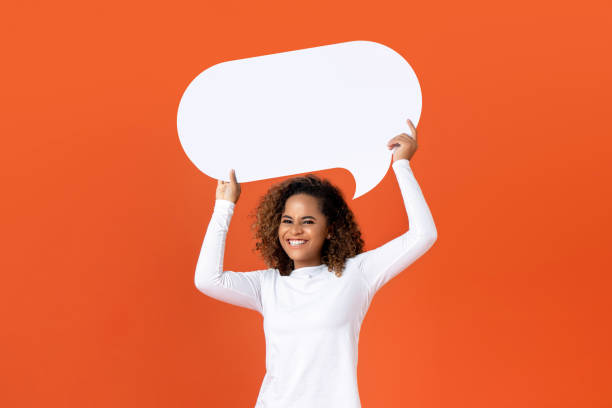 Young African American woman holding empty speech bubble stock photo