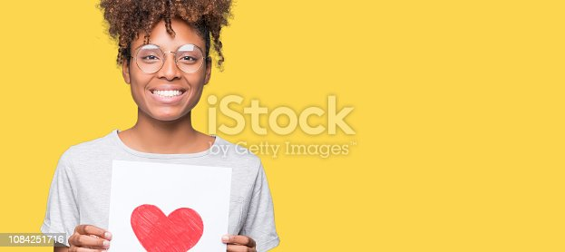 Young african american woman holding paper with red heart over isolated background with a happy face standing and smiling with a confident smile showing teeth