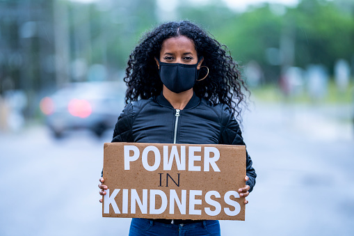Powerful female holding a protest sign that says,