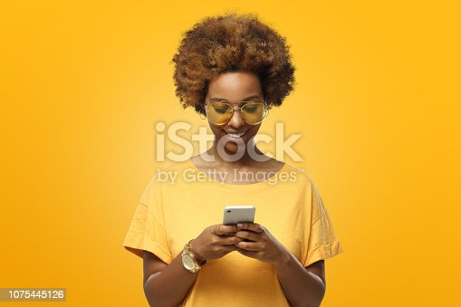 Young african american woman in yellow t-shirt and trendy eyeglasses looking at screen of phone and smiling nicely while chatting