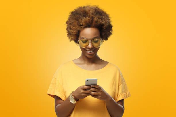 jeune femme afro-américaine en jaunes lunettes de t-shirt et trendy en regardant l'écran du téléphone et souriant gentiment tout en bavardant - monochrome image teintée photos et images de collection