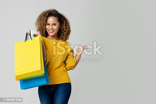 Young happy  African American smiling cheerfully with her shopping bags isolated on light gray background with copy space