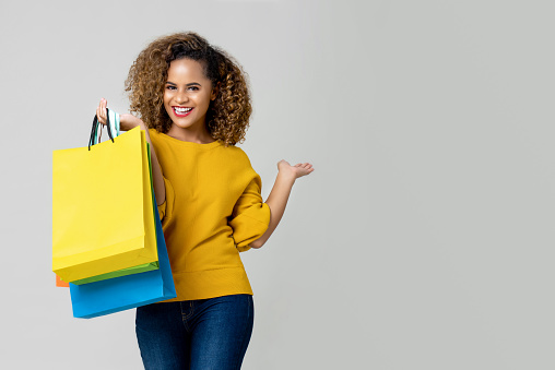 istock Young African American woman is holding shopping bags 1155467348
