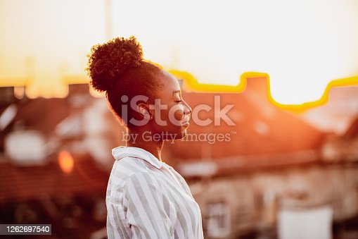 Young African American woman is on the balcony at sunset
