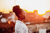 istock Young African American woman is relaxing on the rooftop 1262697540