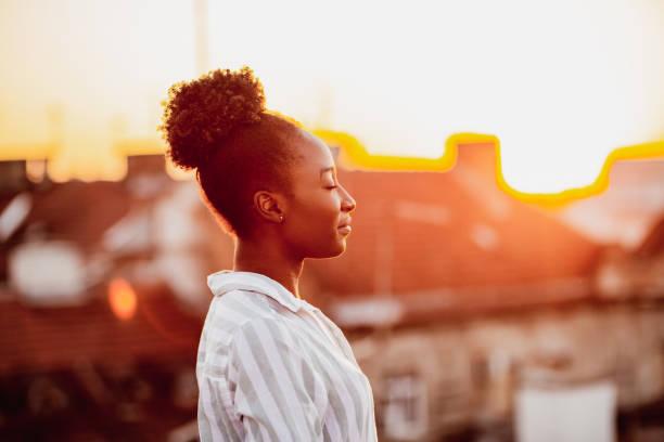 junge afroamerikanische frau entspannt sich auf dem dach - geistige gesundheit stock-fotos und bilder