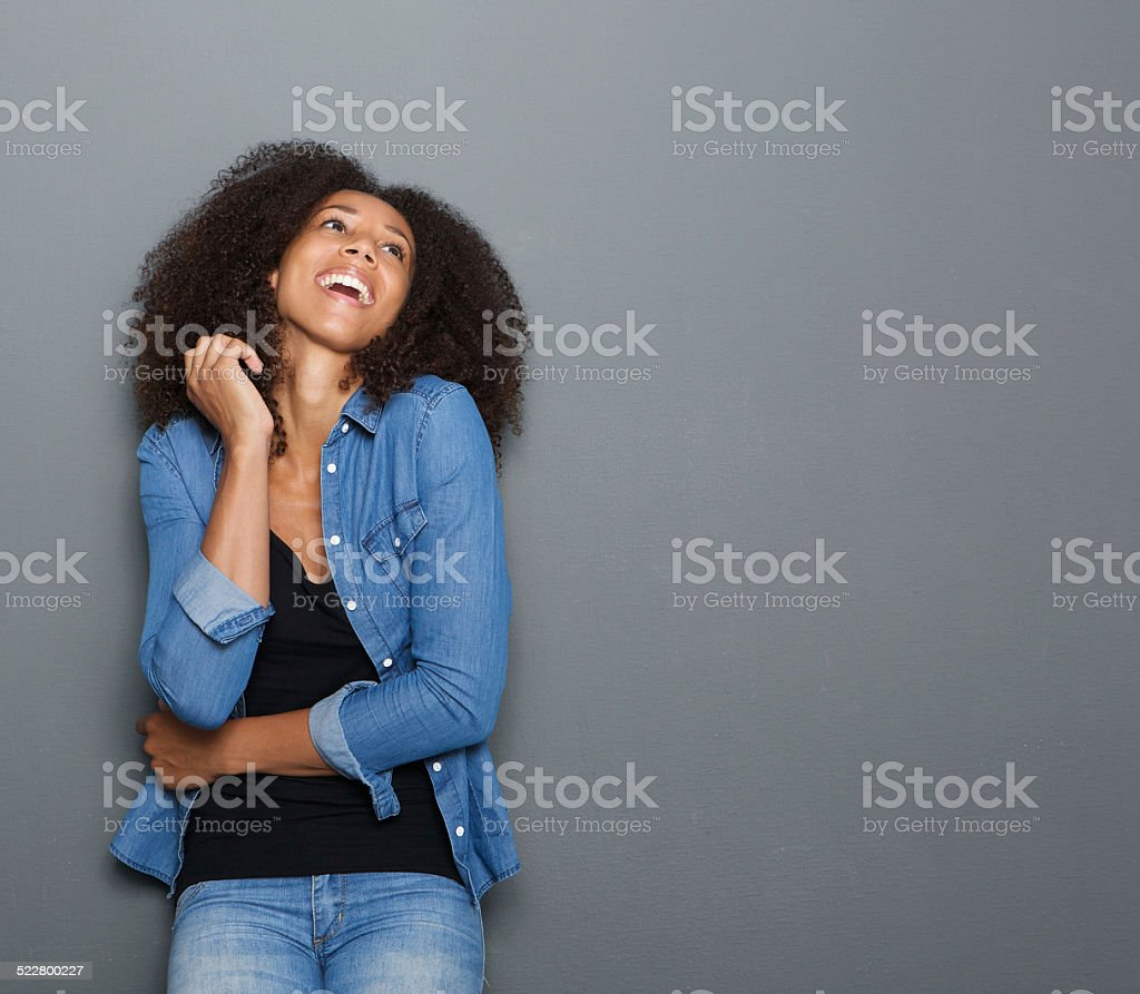 Young african american woman laughing on gray background stock photo