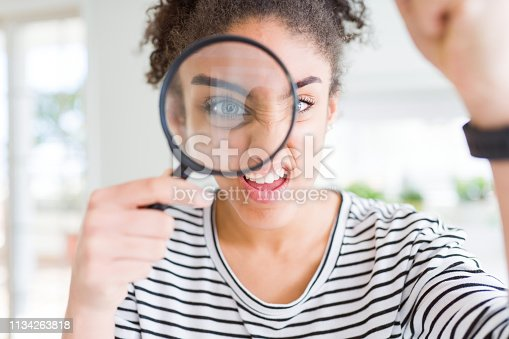 808681534 istock photo Young african american woman looking through magnifying glass annoyed and frustrated shouting with anger, crazy and yelling with raised hand, anger concept 1134263818