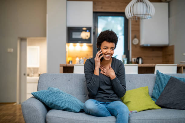 Young African American woman making a phone call and sitting on the sofa Young African American woman making a phone call and sitting on the sofa relief emotion stock pictures, royalty-free photos & images