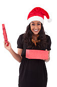 Young African American woman wearing a santa hat opening a gift box, isolated on white background