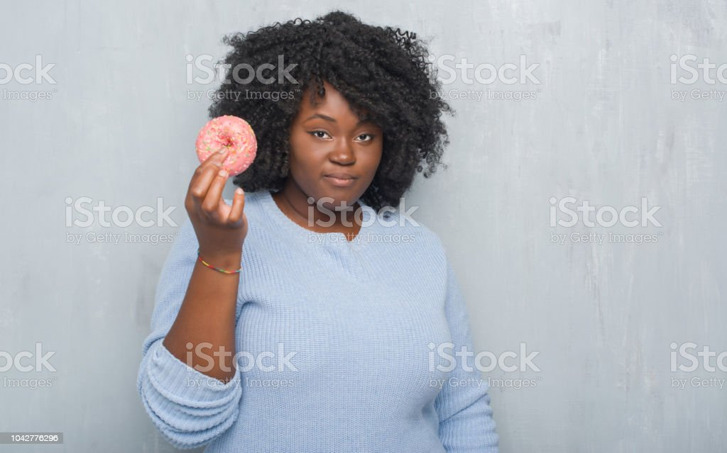 a422e5474c4 Young african american woman over grey grunge wall eating pink donut with a confident  expression on