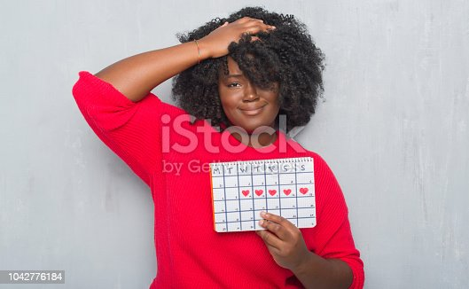 Young african american woman over grey grunge wall holding menstruation calendar stressed with hand on head, shocked with shame and surprise face, angry and frustrated. Fear and upset for mistake.