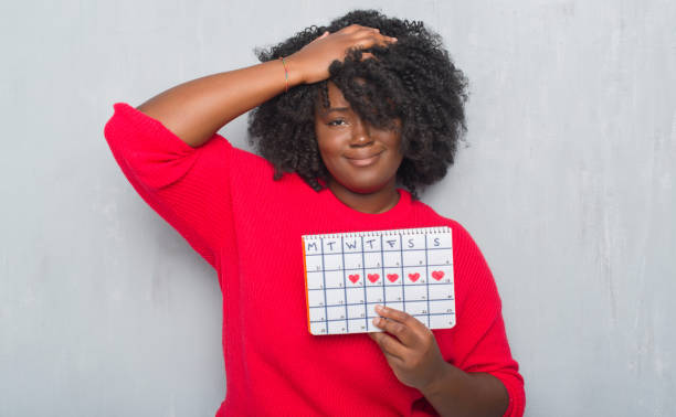 young african american woman over grey grunge wall holding menstruation calendar stressed with hand on head, shocked with shame and surprise face, angry and frustrated. fear and upset for mistake. - mestruazione foto e immagini stock