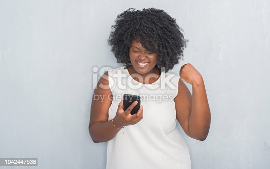 Young african american woman over grey grunge wall texting a message using smartphone screaming proud and celebrating victory and success very excited, cheering emotion