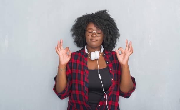 junge afrikanische amerikanerin über graue grunge mauer mit kopfhörern entspannen und lächelnd mit augen geschlossen meditation geste mit den fingern zu tun. yoga-konzept. - one song training stock-fotos und bilder