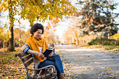 istock Young African American woman reading a book in the public park. 1289287134